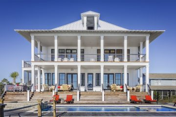 Two story beach house with pool, double porch, and tin roof