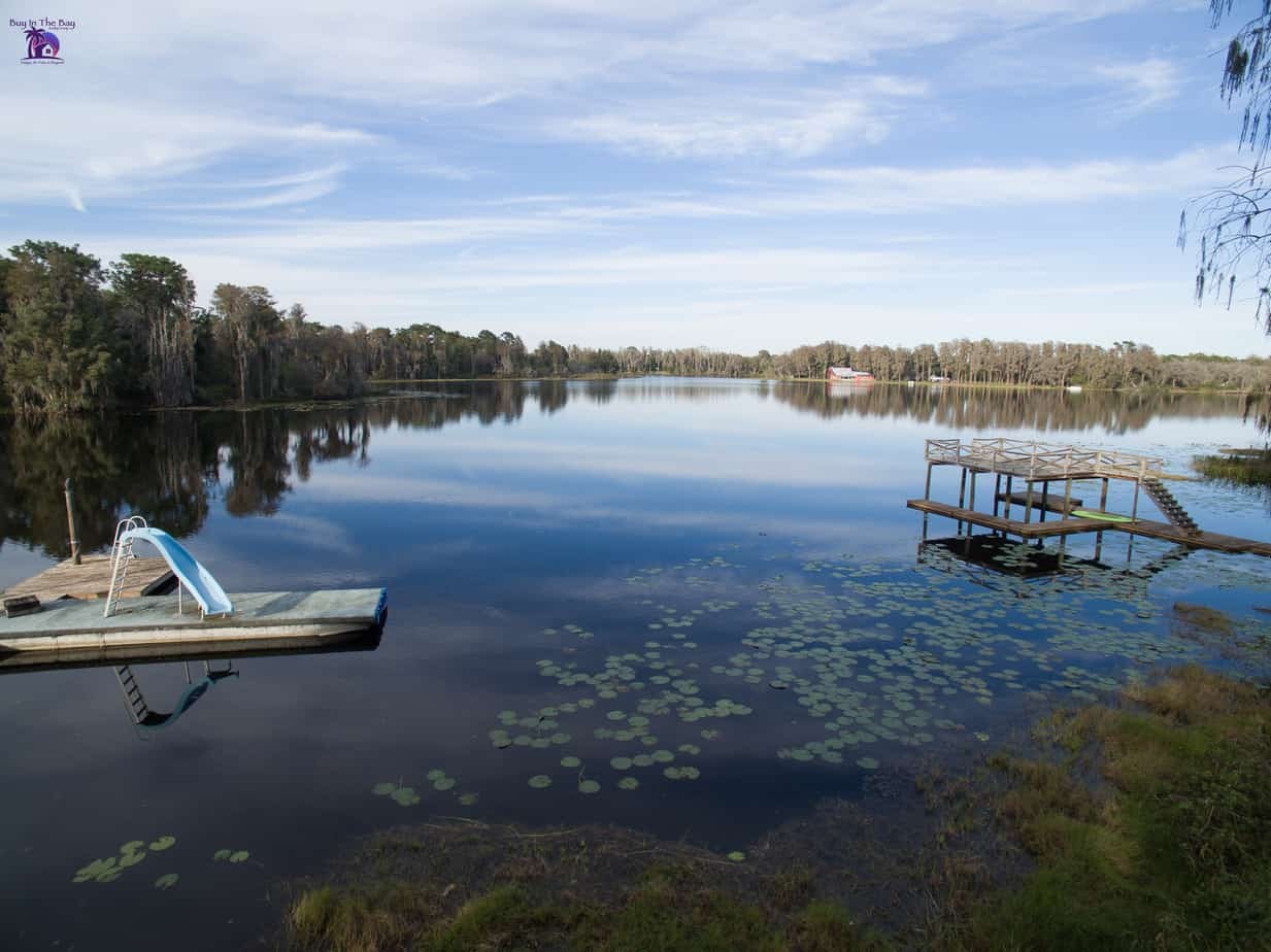 picture of rainbow lake in ofessa florida with trees and a floating slide