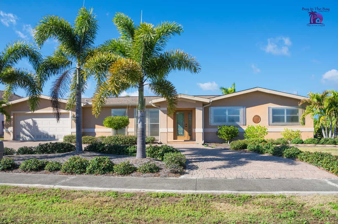 ranch style home that is tan with palm trees, similar to what would be found in Brandon FL