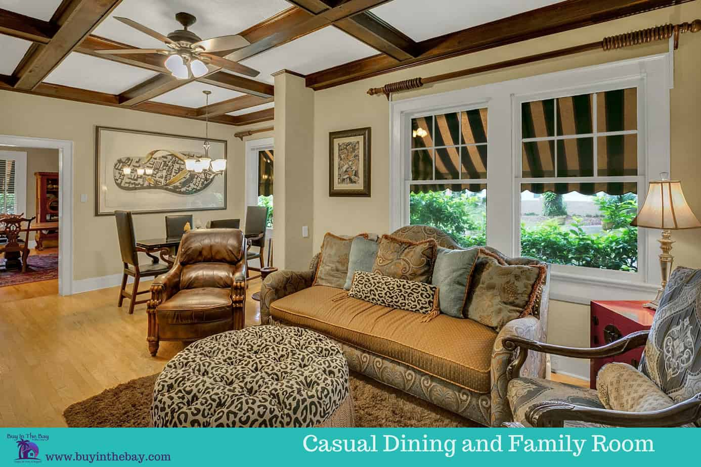 Picture of the cozy family room with couch, two chairs, wood floors, rug, beamed ceilings, for the home for sale at 4024 W Bay to Bay Boulevard Tampa FL 33629. A perfect Example of a Historic Homes in Florida and a Tampa Bay Luxury Homes For sale.