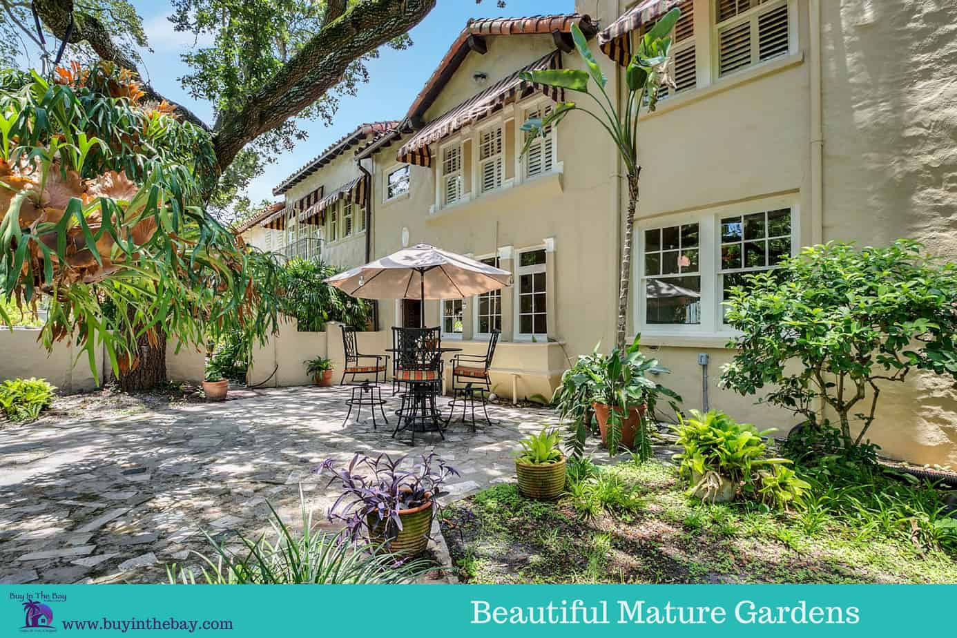 Image of Side of Home and Beautiful Mature Gardens and a table with chairs at the home at 4024 W Bay To Bay Blvd, Tampa FL 33629. A perfect Example of a Historic Homes in Florida and a Tampa Bay Luxury Homes For sale.
