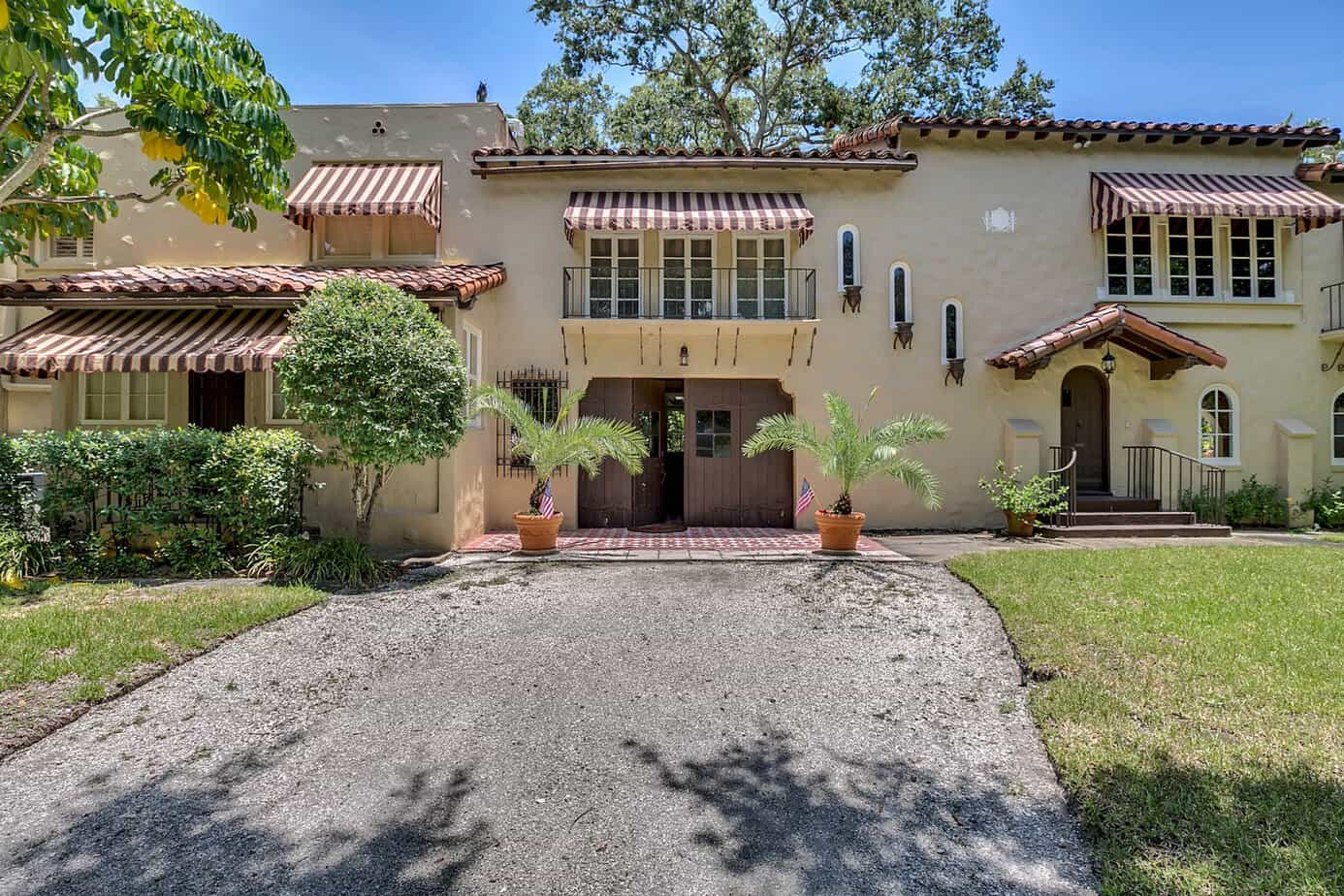 Exterior of luxury florida Mediterranean home with driveway, grass, balconies, windows, and tile barrel roof