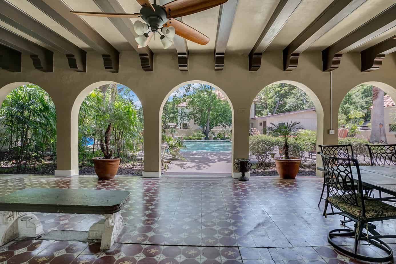 Loggia with beamed ceilings, red mosaic tile, five arched doors with view of pool, and outdoor table for the home for sale at 4024 W Bay to Bay Tampa FL 33629