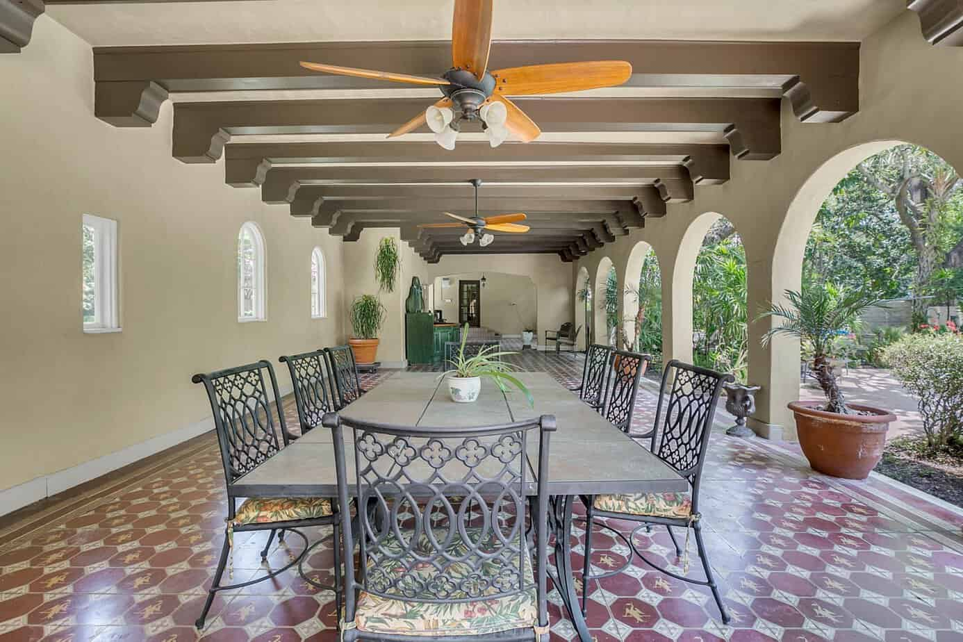 Loggia with beamed ceilings, red mosaic tile, five arched doors, and outdoor table for the home for sale at 4024 W Bay to Bay Tampa FL 33629