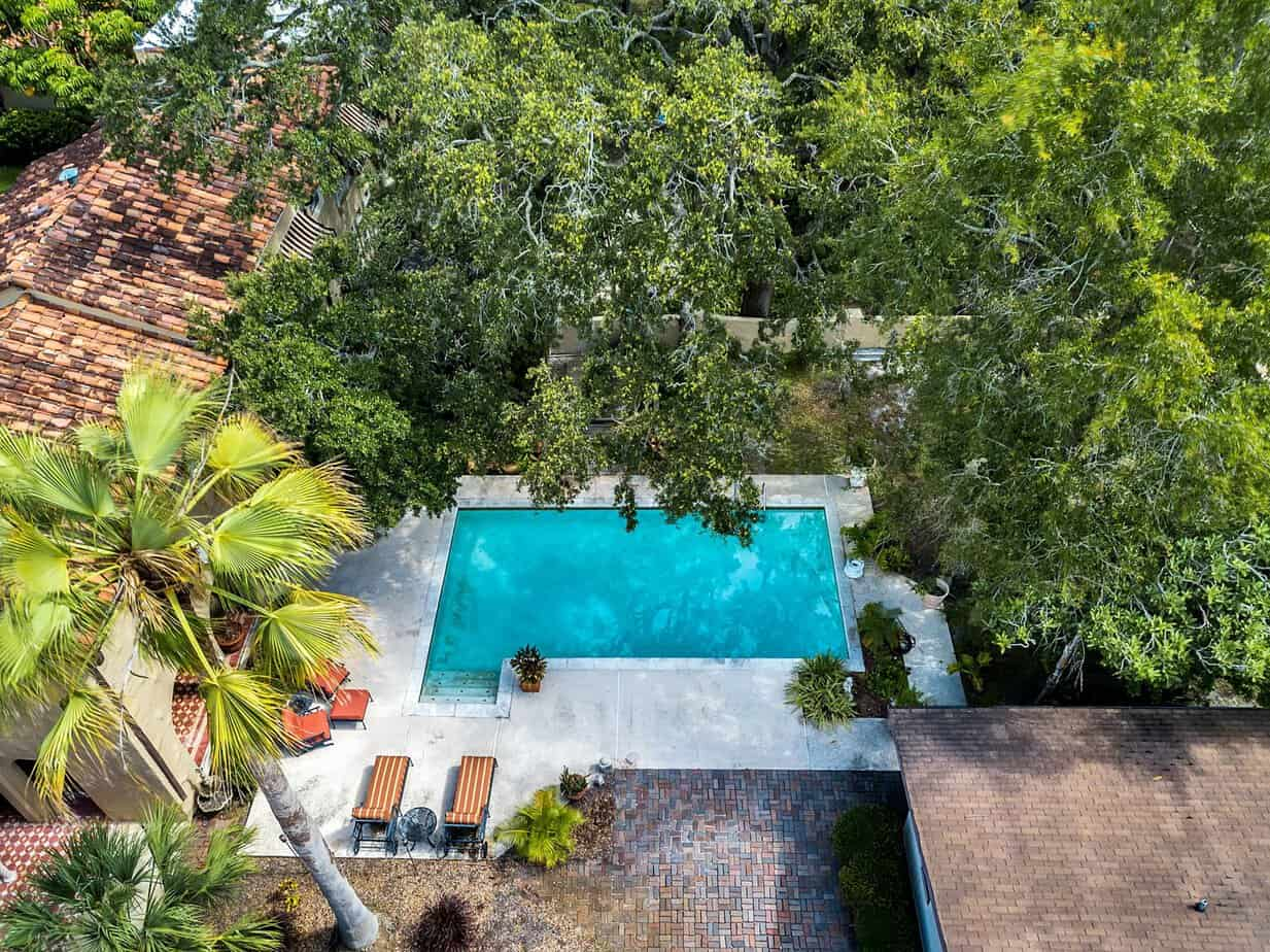 Ariel view of pool with two lounge chairs, and surrounded by palm trees for the home for sale at 4024 W Bay to Bay Tampa FL 33629