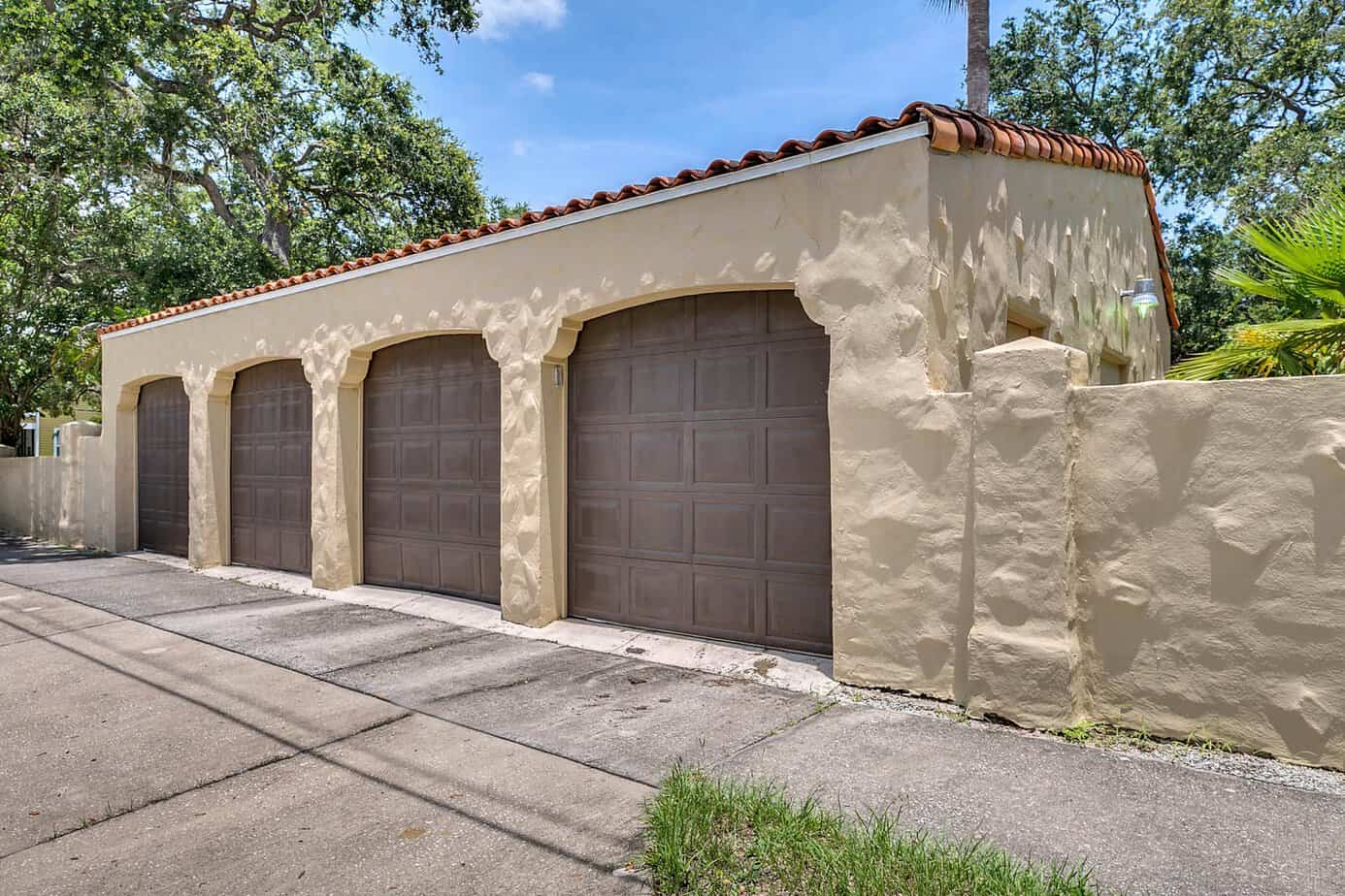 Image of tan garage with four brown doors and red tile barrel roof for the home for sale at 4024 W Bay to Bay Tampa FL 33629