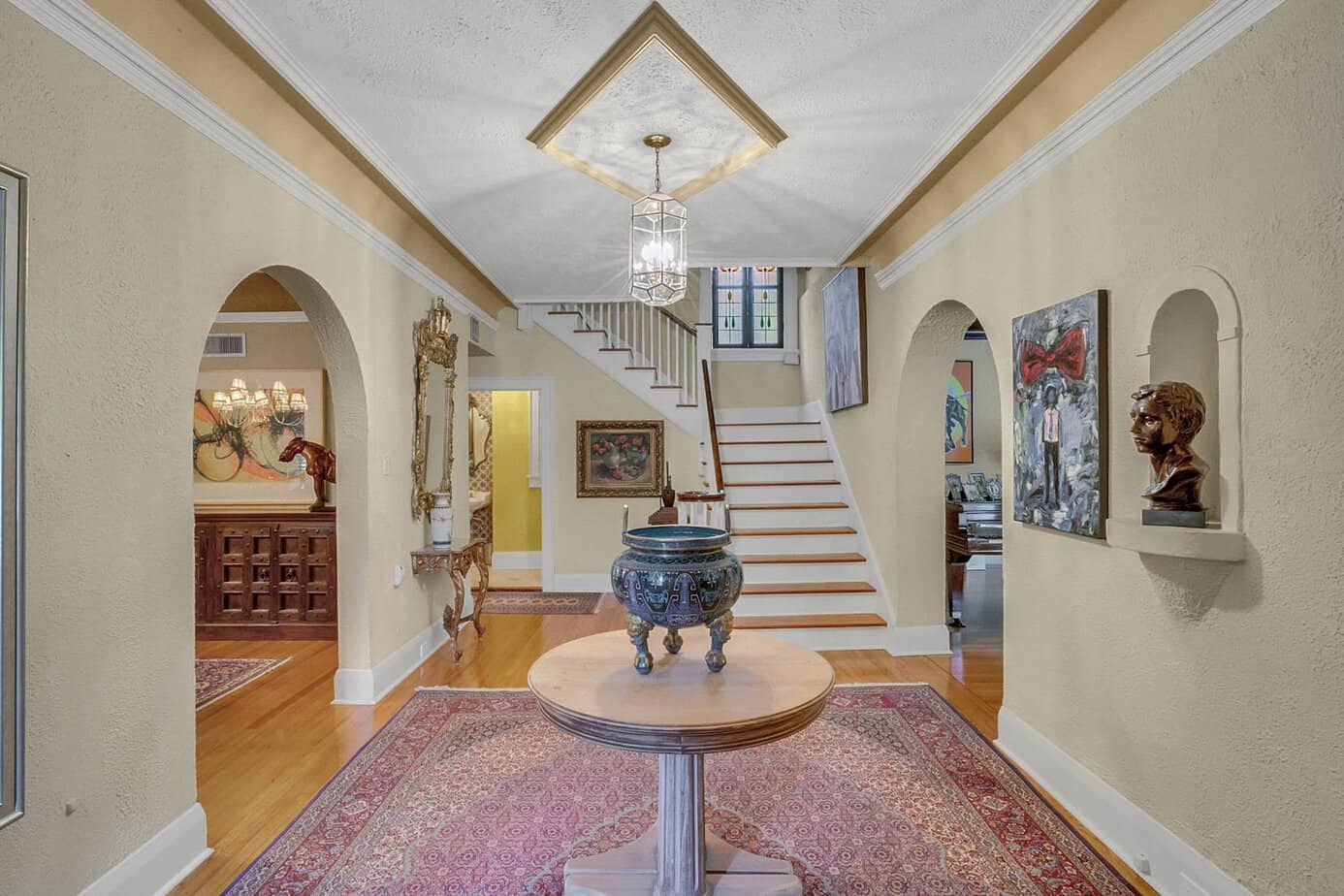 Image of the 13 x 16 foyer with a red rug, wood floors, staircase, and two arched doors, and table in middle for the home for sale at 4024 W Bay to Bay Tampa FL 33629