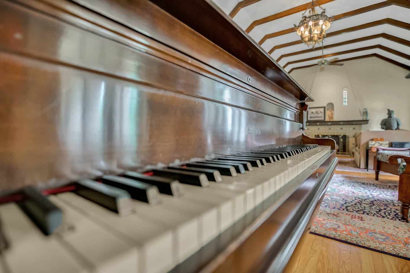 Picture upclose of grand Piano piano in a grand room measuring 35x20 beamed with two chairs, blue rugs, decorative spanish fire place, and arched windows in the home for sale at 4024 W Bay to Bay Tampa FL 33629