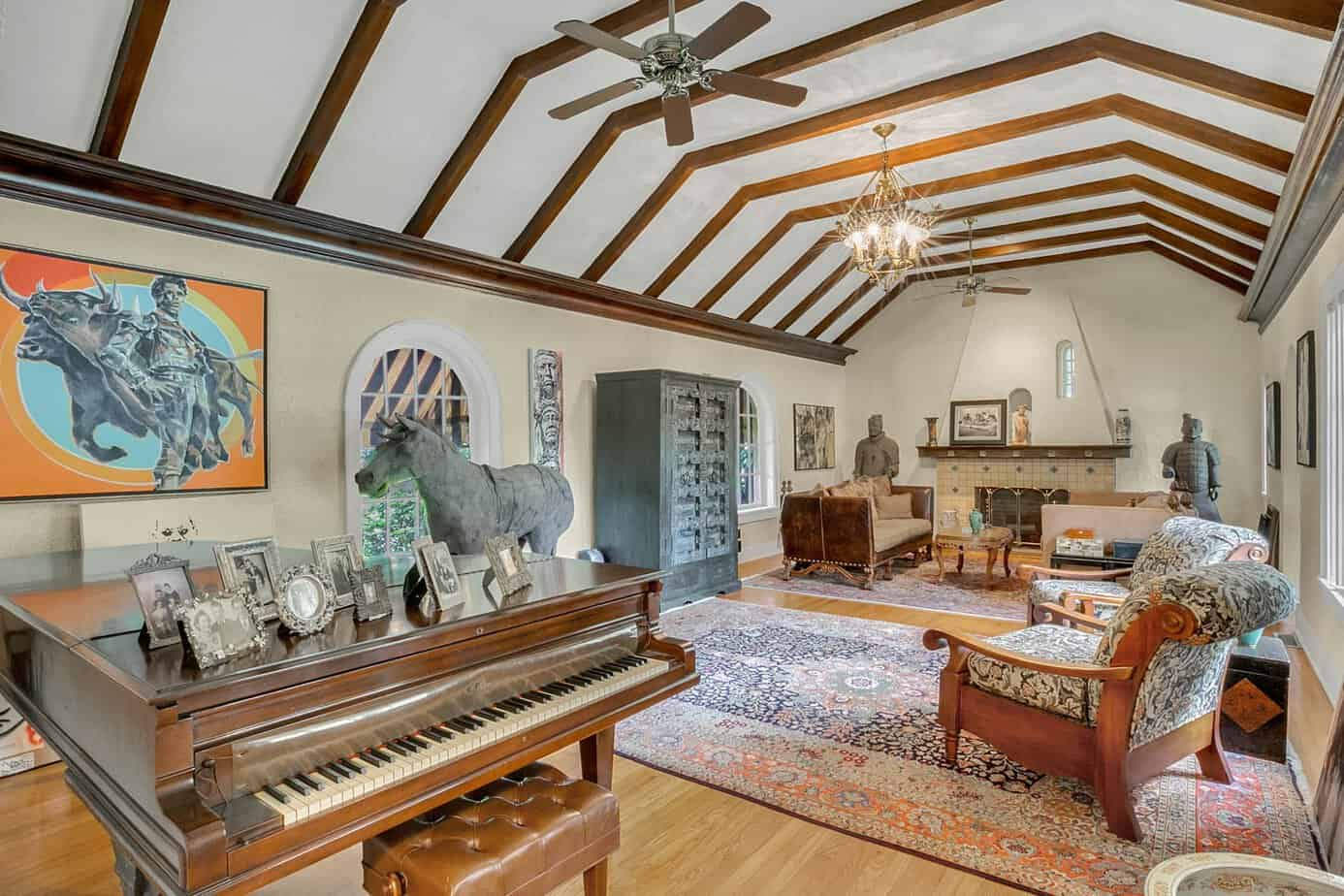 Picture of a grand room measuring 35x20 beamed with two chairs, red and blue rugs, two sofas, decorative spanish fireplace, and arched windows in the home for sale at 4024 W Bay to Bay Tampa FL 33629