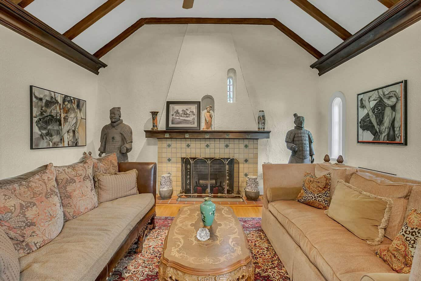 Picture of a grand room measuring 35x20 beamed with two couches, red rugs, decorative spanish fireplace, and arched windows in the home for sale at 4024 W Bay to Bay Tampa FL 33629