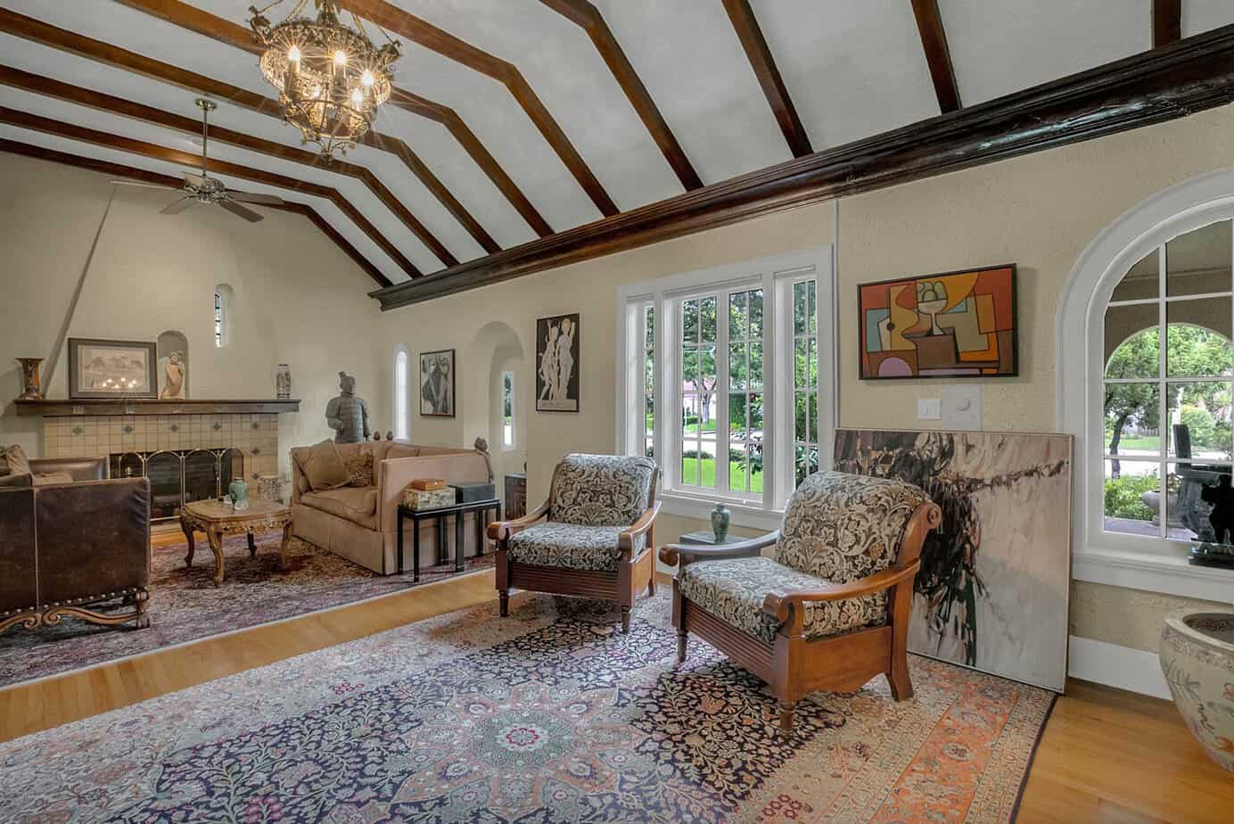 Picture of a grand room measuring 35x20 beamed with two chairs, blue rugs, decorative spanish fire place, and arched windows in the home for sale at 4024 W Bay to Bay Tampa FL 33629