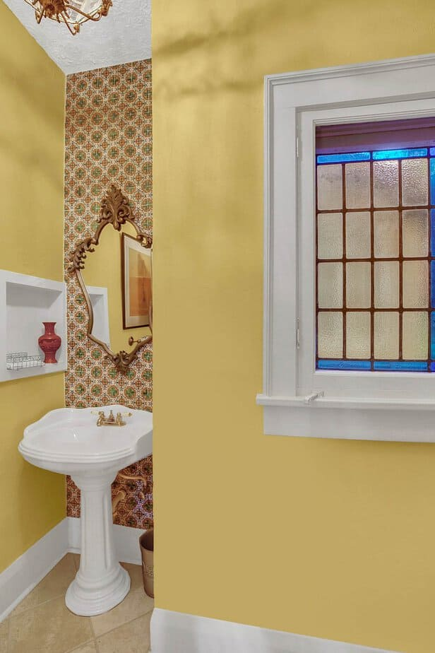 half bath with yellow walls, pedestal sink, and unique glass mosaic window at the home for sale at 4024 W Bay to Bay Tampa FL 33629