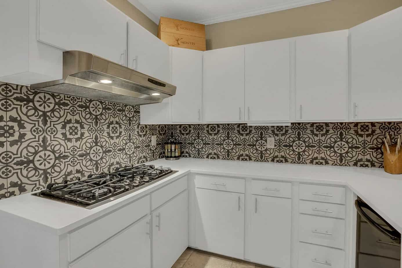 Kitchen with stone counterops, blue mosaic backsplash, Stainless Steel range hood, gas cooktop,, white cabinets and tile floor for the home for sale at 4024 W Bay to Bay Tampa FL 33629