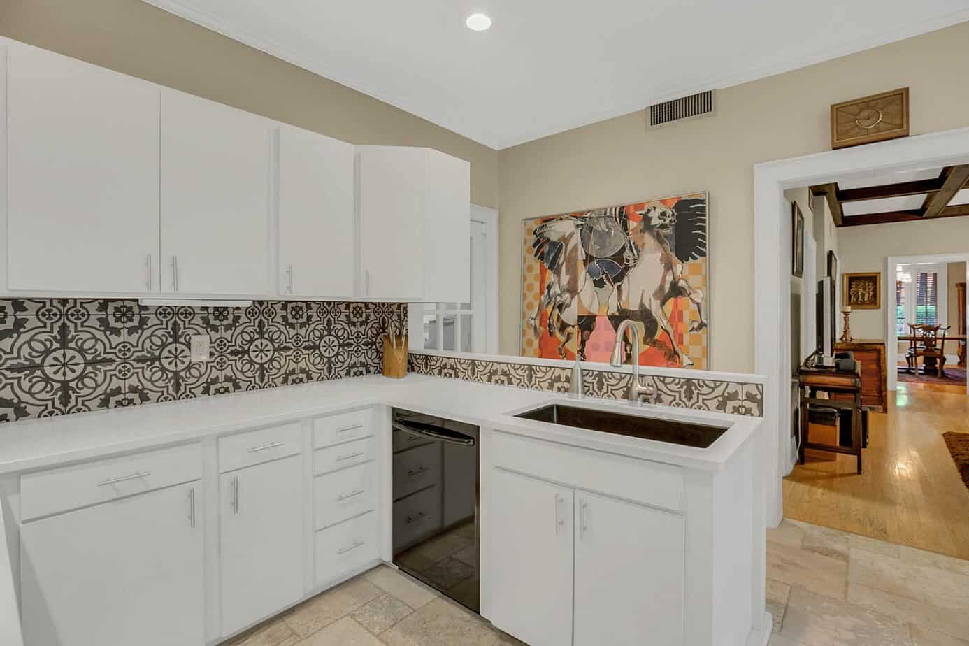 Kitchen with stone counterops, blue mosaic backsplash, black dishwasher, white cabinets and tile floor for the home for sale at 4024 W Bay to Bay Tampa FL 33629
