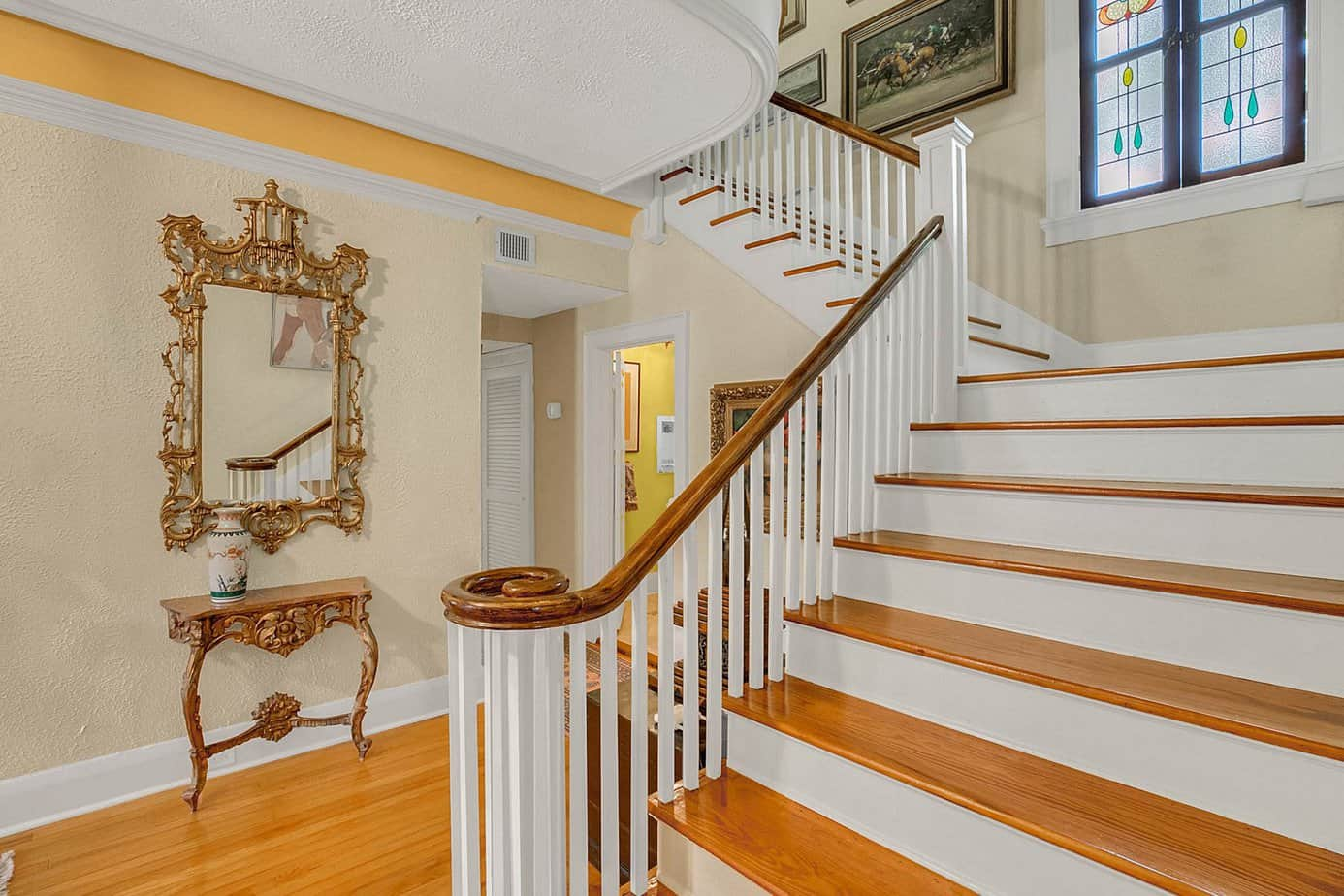 Curving Staircase With Wood Floors, wood stairs, white spindle, and side table for home for sale at 4024 W Bay to Bay Tampa FL 33629