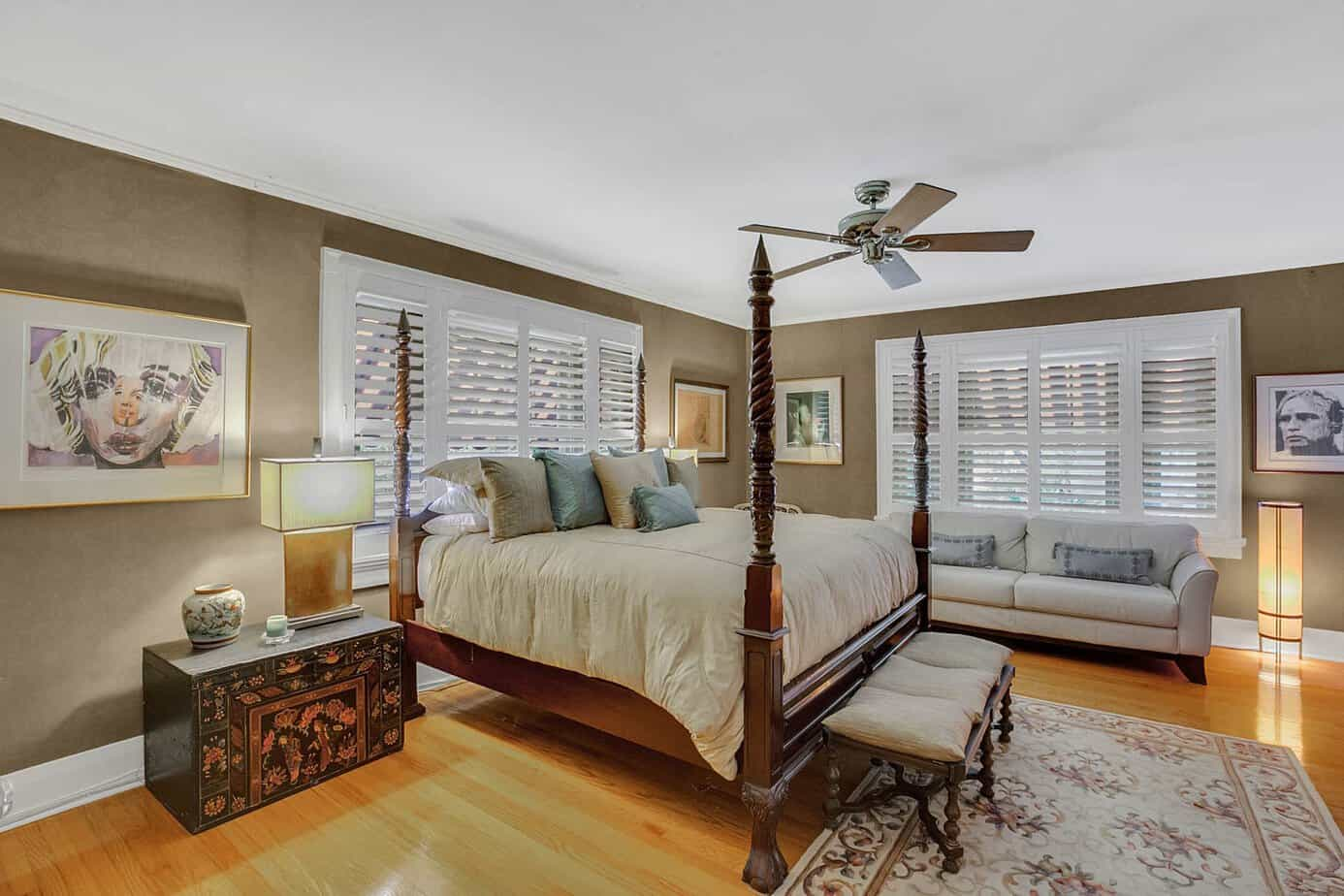 One of the Dual Master bedrooms in the the historic south tampa estate home for sale at 4024 W Bay To Bay Blvd. Tampa FL 33629 with wood floors, two windows, king sized bed, and artwork
