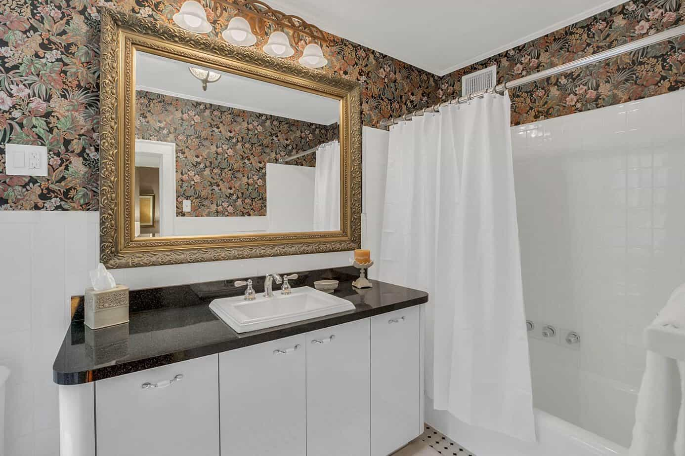 Bathroom with white tub and sink with dark granite, and floral wallpaper for the home for sale at 4024 W Bay to Bay Tampa FL 33629