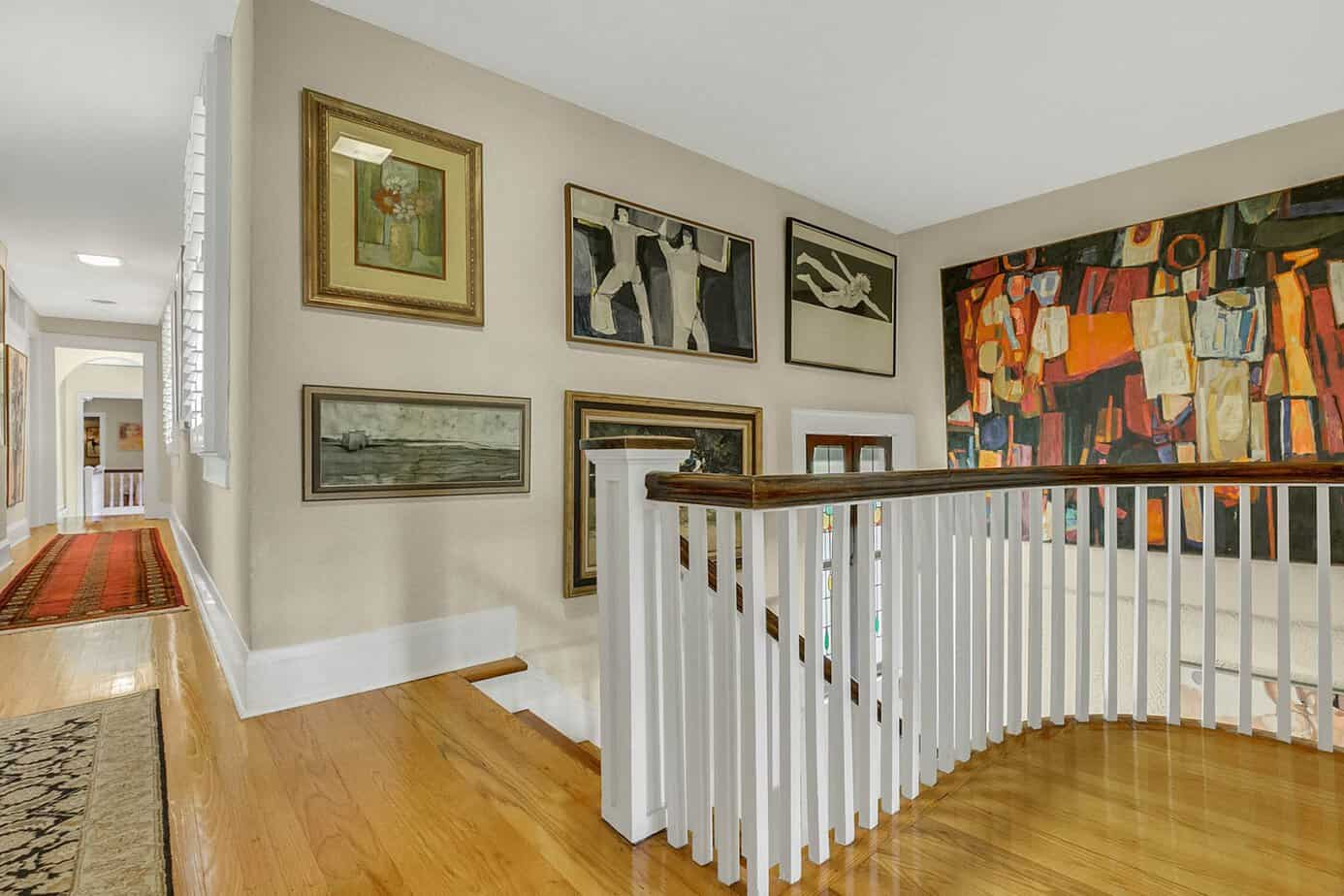 Landing for the front staircase with wood floods, artwork, decorative rugs and white spindles for the home for sale at 4024 W Bay to Bay Tampa FL 33629