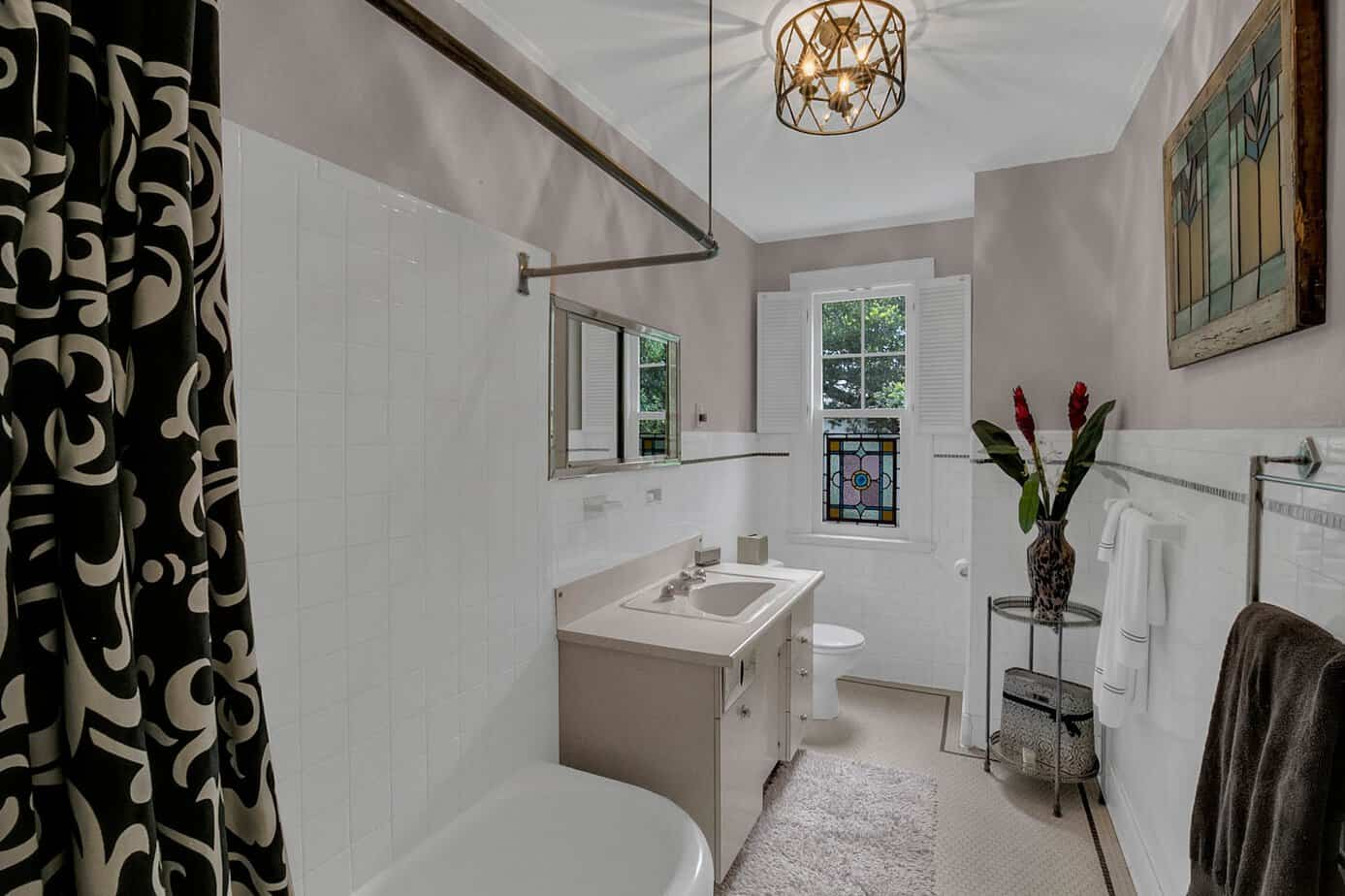 Bathroom with white tub and tile, sink, toilet, and decorative light fixture for the home for sale at 4024 W Bay to Bay Tampa FL 33629