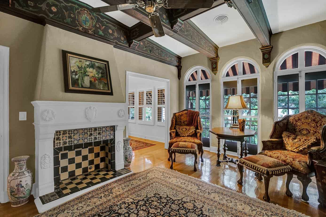 Upstairs Sitting Room with Exquisite Architectural Details And Fireplace, wood floors, decorative rug, and a chair and sofa for the home for sale at 4024 W Bay to Bay Blvd. Tampa FL 33629
