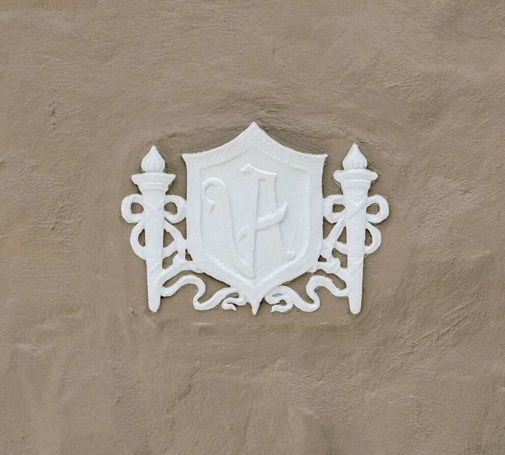 Picture of white Val Maestro Antuano Shield against tan wall, One of Largest Cigar Manufacturers in World that Built this home at 4024 W Bay to Bay Tampa FL 33629