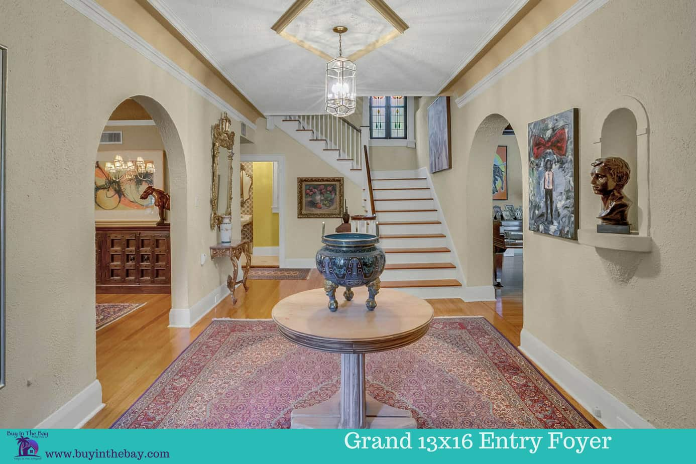 Image of the 13 x 16 foyer with a red rug, wood floors, staircase, and two arched doors, and table in middle for the home for sale at 4024 W Bay to Bay Blvd Tampa FL 33629 a historic Florida Home and a great example of a tampa bay luxury homes for sale. A perfect Example of a Historic Homes in Florida and a Tampa Bay Luxury Homes For sale.