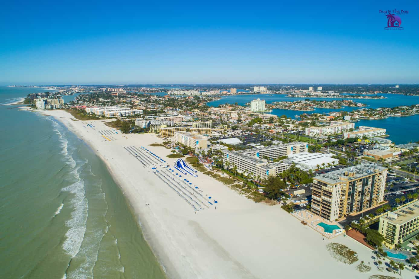 Aerial drone image of hotels and resorts and homes for sale in St Pete Beach Florida with the gulf of mexico on the left, pristine white beach, and hotels