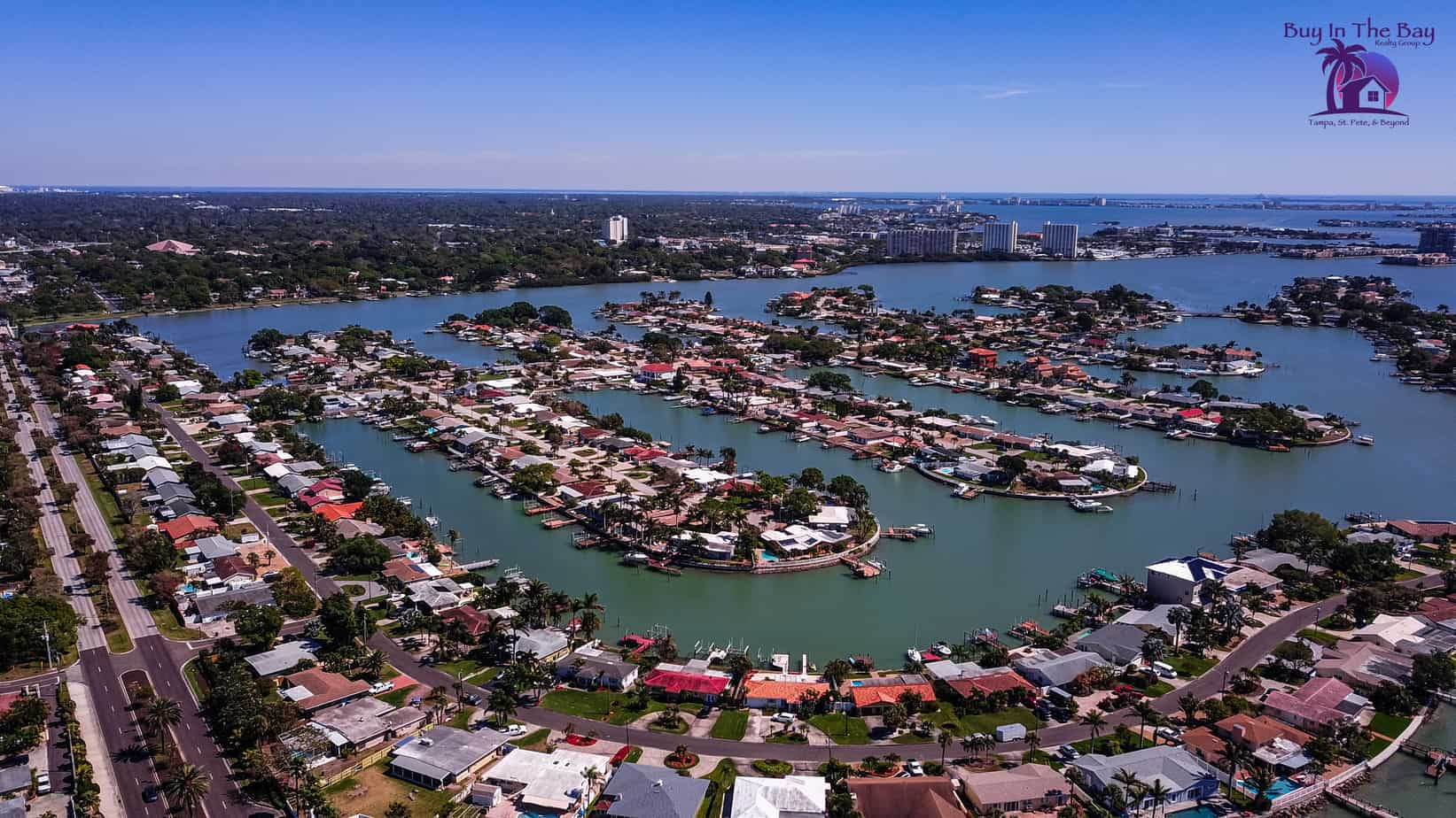 Ariel view of treasure island fl 33706 with many different colored houses on an inlet surrounded by water