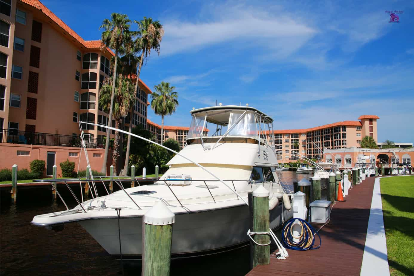 Image of pink condo building on the water with a white yacht tied to a boat slip in a condo community in a similar home for sale in pasadena fl with the zip code of 33707