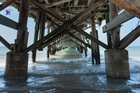 Shows the underneath of the long fishing pier in Redington beach Fl with a below view under the pier and crashing waves