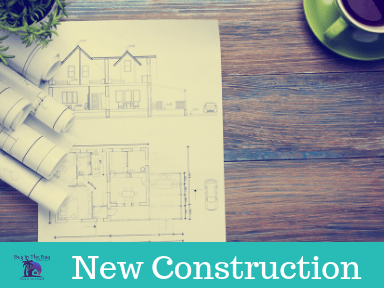 image of a table with coffee cup and blueprints showing new construction