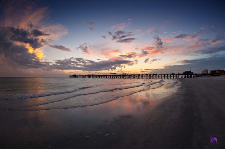 image of a beautiful sunset at north redington beach florida in the zipcode of 33708 with a multicolored sky, reflections on the water, and a shadowed beach