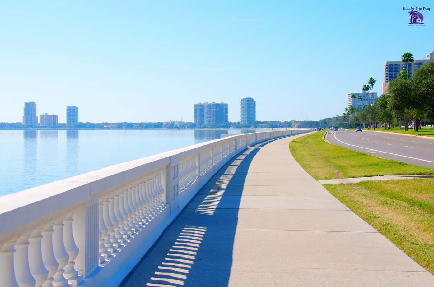 Bayshore Boulevard Tampa Sidewalk with a white fence and water view of tall buildings