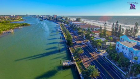 Ariel View of Indian Shores Florida in the zip code of 33785 with a long inlet with multi colored homes with the gulf of mexico on one side and the Narrows inlet on the other side