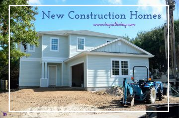 picture showing new homes in florida. house is two story and tan and there is diet and a tractor in the front
