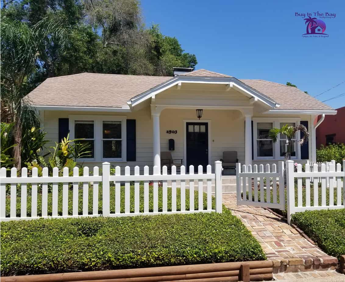 Yellow cottage with white picket fence showing a typical home for sale gulfport fl 33711 and 33707