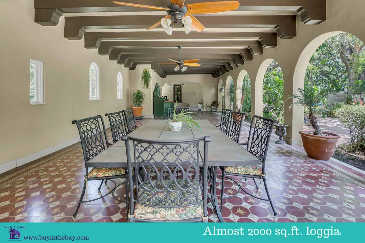 Loggia with beamed ceilings, red mosaic tile, five arched doors, and outdoor table for the home for sale at 4024 W Bay to Bay Blvd Tampa FL 33629. A perfect Example of a Historic Homes in Florida and a Tampa Bay Luxury Homes For sale.