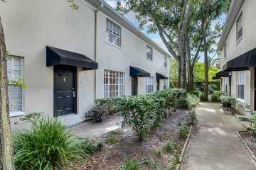 Front of 408 S Arrawana Ave #c3 Tampa FL 33609 with a tan ecterior, black door, and 2 levels.