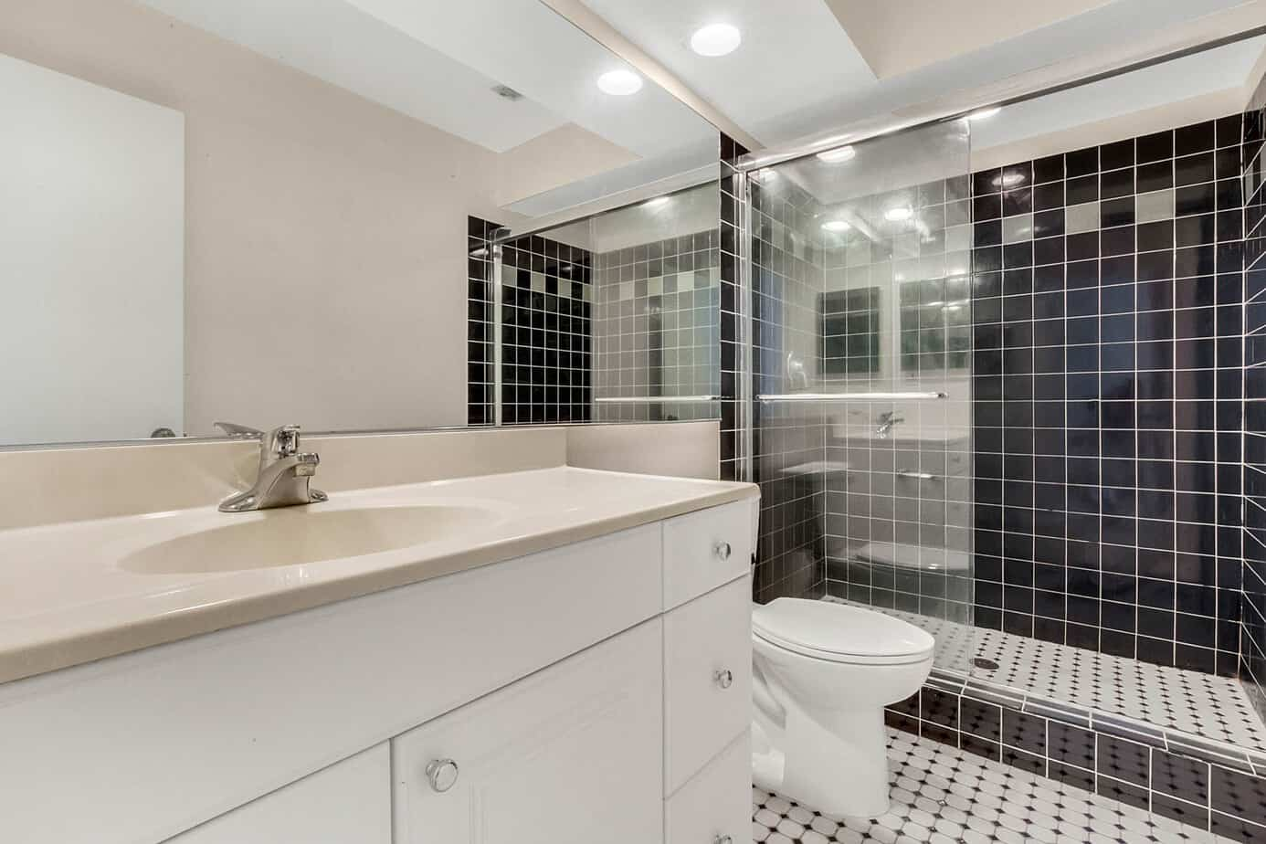 image of bathroom at 408 S Arrawana Ave Tampa FL 33609 with black tiles and white cabinets